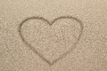 Heart shape symbol drawn in sand Stock Photography