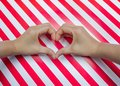 Heart shape of two hand put on striped pattern red & white placemats
