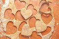 Heart shaped biscuits cookie cutter on raw cookie dough with a few cookies Stock Image
