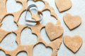 Heart shaped biscuits cookie cutter on raw cookie dough with a few cookies Stock Images