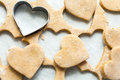 Heart shaped biscuits cookie cutter on raw cookie dough with a few cookies Stock Photos