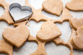 Heart shaped biscuits cookie cutter on raw cookie dough with a few cookies Royalty Free Stock Images