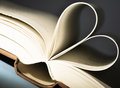Heart shaped book pages of a curved into a in front of blue background Royalty Free Stock Image