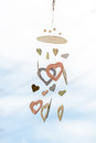 Heart shaped ceramic wind chimes hanging on window and defocused Royalty Free Stock Photo