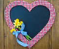 Heart-shaped chalkboard and fresh daffodils Stock Photos