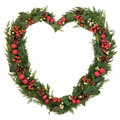 Heart shaped christmas wreath with red bauble decorations holly mistletoe and winter greenery over white background Stock Photography