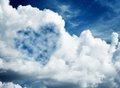 Heart shaped cloud on blue sunny sky. Royalty Free Stock Photo