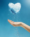 Heart shaped cloud rain storm a hand holding a coming from a Royalty Free Stock Photography