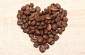 Heart shaped coffee beans on wooden background closeup of valentine of grains Royalty Free Stock Photo