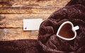 Heart shaped coffee cup, cozy brown scarf, blank paper tag Royalty Free Stock Photo