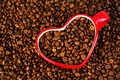 Heart shaped coffee mug with beans sinked in coffeen valentines day Royalty Free Stock Images