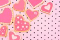 Heart shaped cookies hand decorated on pink patterned background Stock Photos