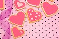 Heart shaped cookies hand decorated with ribbon on pink patterned background Royalty Free Stock Photo