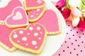 Heart shaped cookies plate of with pink frosting flowers and pink pattered background Stock Photo