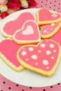 Heart shaped cookies plate of with pink frosting and pink pattered background Royalty Free Stock Images