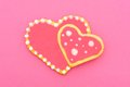 Heart shaped cookies two overlapping homemade over a pink background Stock Photos