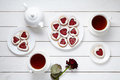 Heart shaped cookies for Valentines day with teapot, two cups of tea and rose composition Royalty Free Stock Photo