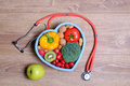 Heart shaped dish with vegetables and stethoscope Royalty Free Stock Photo
