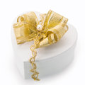 Heart shaped gift box with gold bow white cardboard tied an elegant braid and pearl for surprising a loved one on christmas Stock Photography