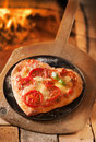 Heart shaped italian pizza romantic on a platter and wooden board with the fire of a oven visible behind Stock Photo