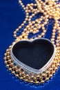 Heart shaped jewel box with golden beads Royalty Free Stock Images