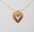 Heart shaped necklace gold chain green emerald stone Stock Photo
