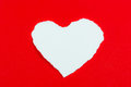 Heart shaped rip paper white on over red background Royalty Free Stock Image