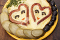 Heart shaped sausages with fried eggs pickles and olives Royalty Free Stock Image