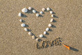 Heart shaped sea shells and drawing letter love on the sand beach Royalty Free Stock Photo