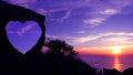 Heart-shaped stone on a mountain with purple sky sunset. Royalty Free Stock Photo