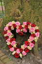 Heart shaped sympathy flowers near a tree Stock Photo