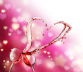 Heart splash from two glasses of red wine on abstract small lights background Stock Photo