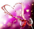 Heart splash from two glasses of red wine over abstract hearts light background Royalty Free Stock Photos