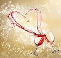 Heart splash from two glasses of red wine over golden light background Stock Photo
