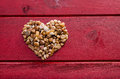 Heart of stone consists small stones on a surface red wood Royalty Free Stock Photos