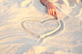 Heart symbol drawn in the sand hand girl drawing a Stock Photography
