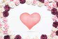 Red ribbon heart symbol with pink roses on white wooden table