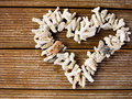 Heart symbol on wooden background seashells in the shape of a Stock Images