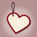 Heart tag red cardboard shape hanging on the pink wall Royalty Free Stock Photo