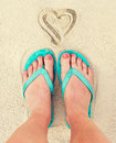 Heart and woman feet wearing flip flops in the sand of a beach