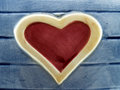 close-up red heart with yellow frame on artificial blue wood plank made of painted pottery ceramic statue Royalty Free Stock Photo