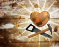Heart of wood with a saw and hammer Stock Image
