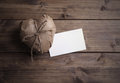 Heart wrapped in brown kraft paper with a note on wooden background Royalty Free Stock Image
