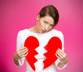Heartbreak closeup portrait young troubled sad confused woman holding broken heart in hands about to cry isolated pink background Royalty Free Stock Photography