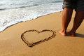 Heartin on beach sand man standing near. Royalty Free Stock Photos