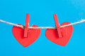 Hearts on clothesline with clothespins, blue background Royalty Free Stock Images