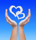 Hearts from clouds in hands Royalty Free Stock Photo