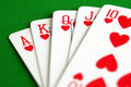 Hearts royal flush poker playing cards over green table Royalty Free Stock Images