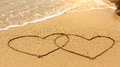 Hearts in the sand drawn by hand in the surf. Love. Royalty Free Stock Photo