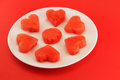 Hearts of watermelon on a plate conceptual image for san valentine s day with chunks cut heart shaped and presented Royalty Free Stock Image